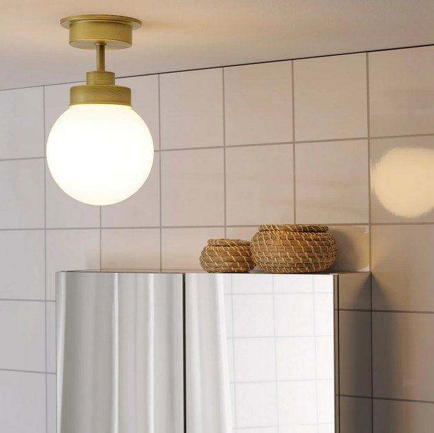 IKEA bathroom lighting idea with brass ceiling light and white tile wall