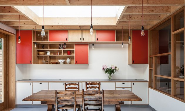 red kitchen cabinet color with warm wood and rustic dining table