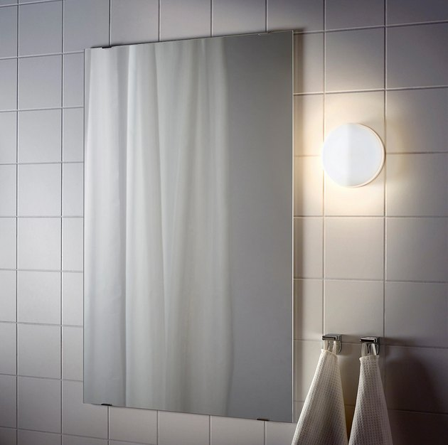 IKEA bathroom lighting idea with white tile wall and wall light