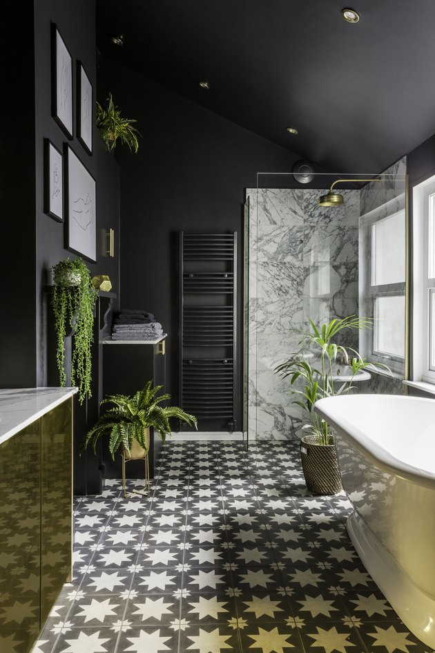 art deco bathroom by Gold Is a Neutral with black walls and patterned floor tile