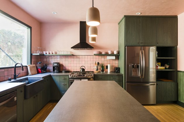 view of kitchen island with dark countertop, green kitchen cabinets, stainless steel appliances and pink walls and backsplash