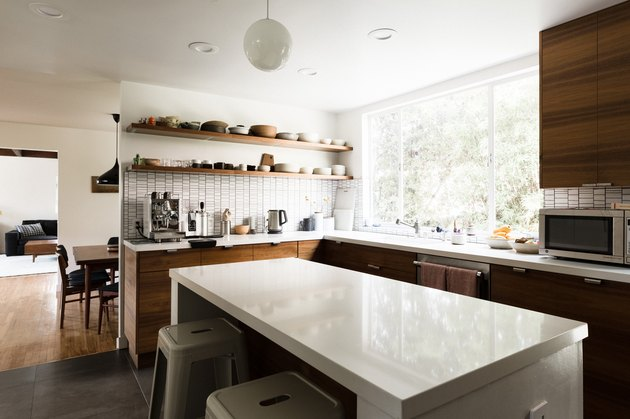 kitchen island with white stone countertop; dark wood kitchen cabinets; open concept to dining room