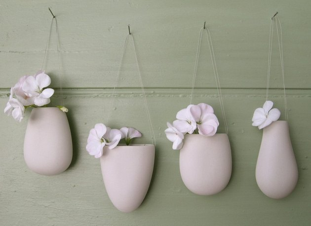 four white porcelain flower bud vessels that are decorative accents