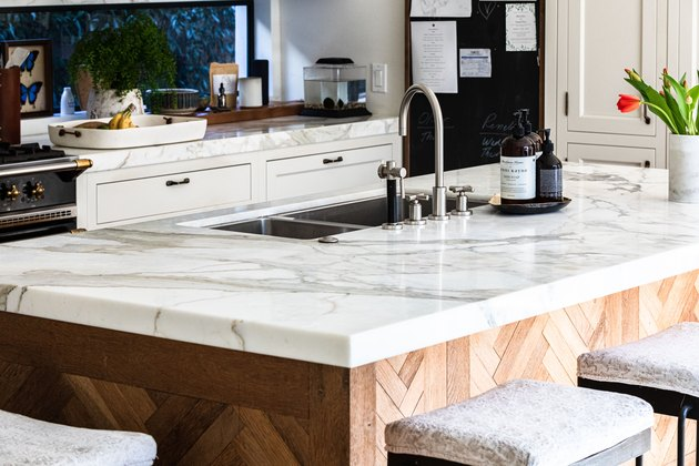 kitchen island with double handle faucet and marble countertop