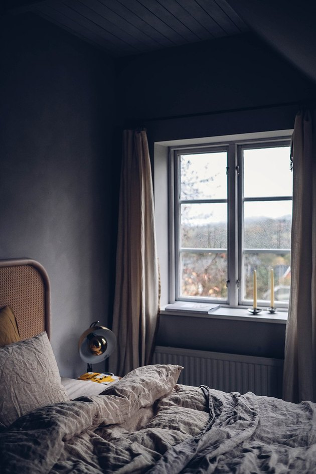 rattan bed in dark minimalist bedroom with linen duvet cover
