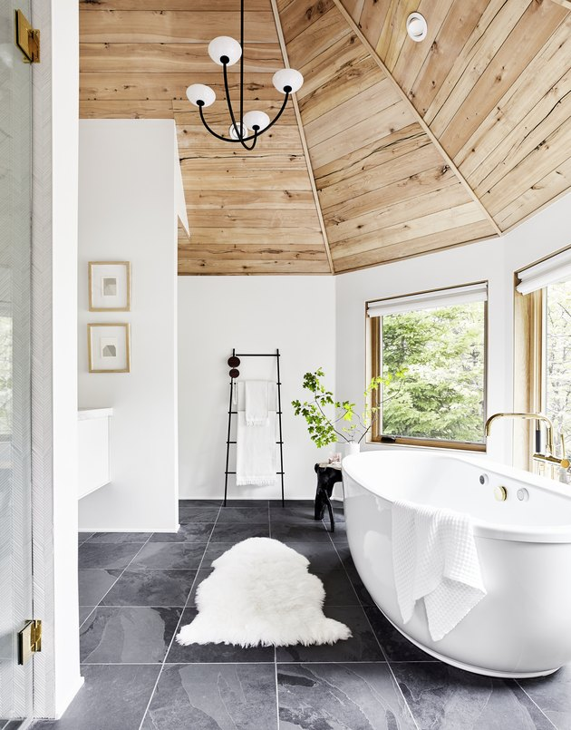 rustic bathroom lighting idea with modern chandelier hanging from wood ceiling