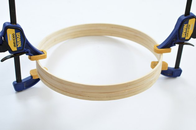 Blue and yellow hand clamps holiding together wooden hoops.