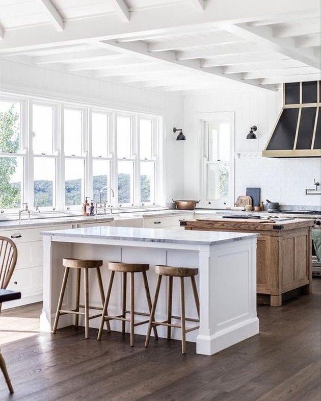 white farmhouse kitchen with white island and wooden island