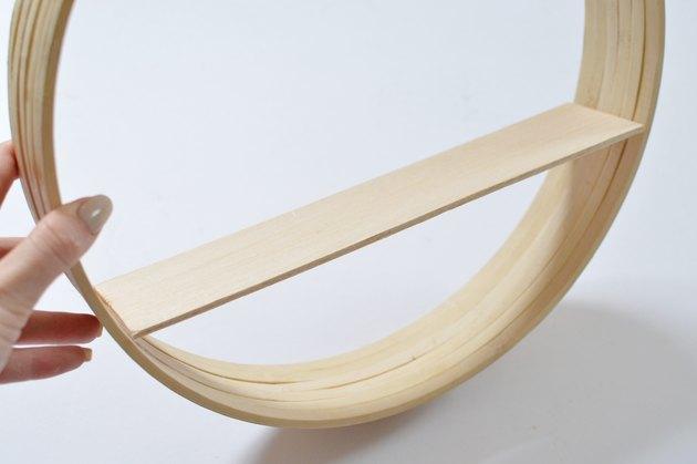 Étagère en bois placée à l'intérieur du cadre circulaire