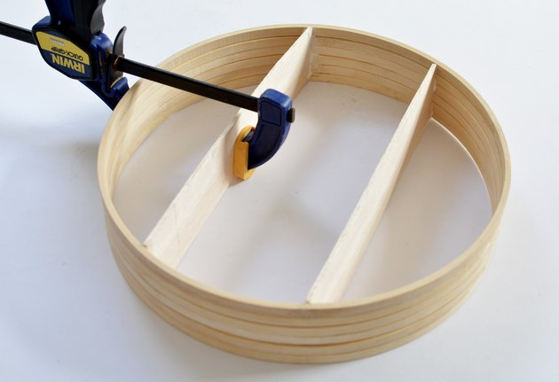Wooden circular shelf with hand clamp holding shelf while glue dries.
