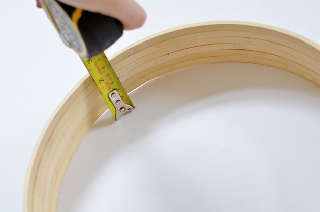 Tape measure extended to measure wooden hoops.