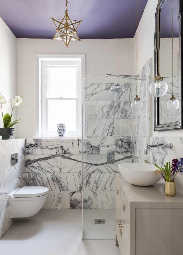 purple bathroom with marble clad wall
