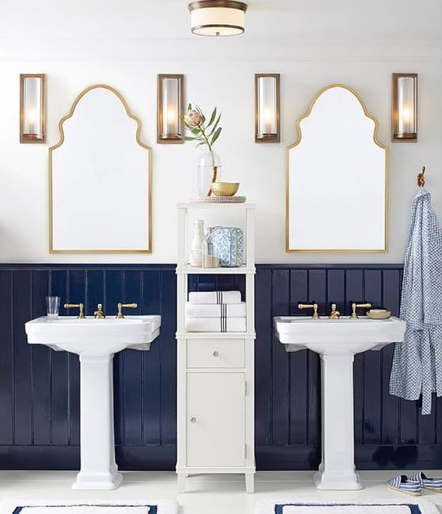 Brass and white coastal bathroom lighting idea with accompanying wall sconces in white and navy blue bathroom