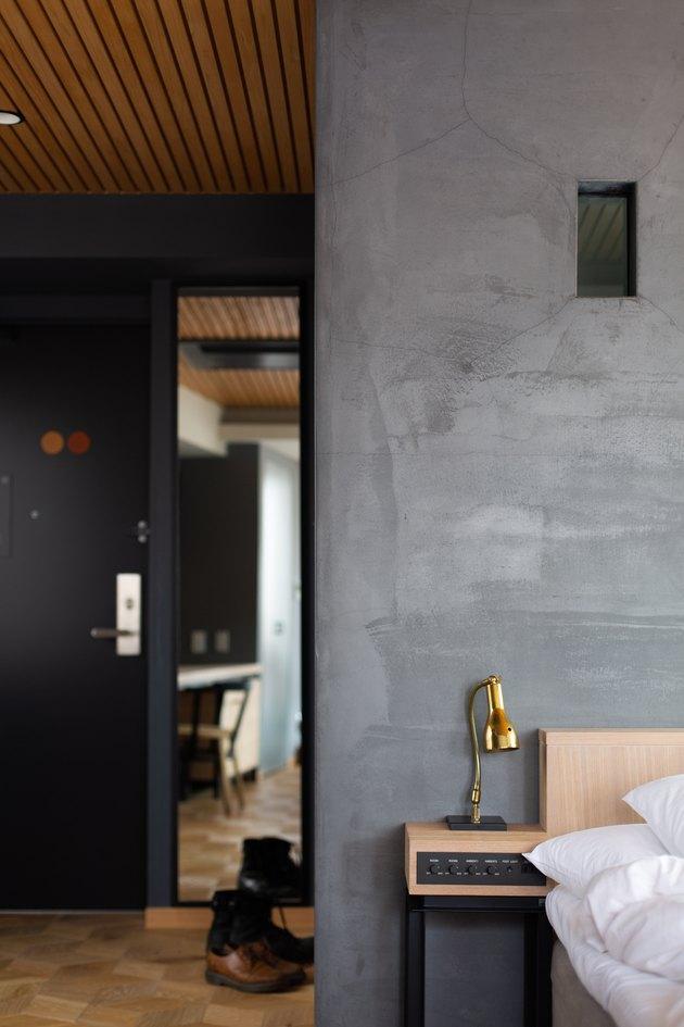 dark minimalist bedroom with gold lamp and rustic wood floor