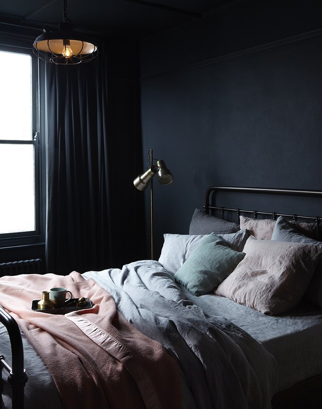 dark minimalist bedroom with seafoam bedding and pink blanket