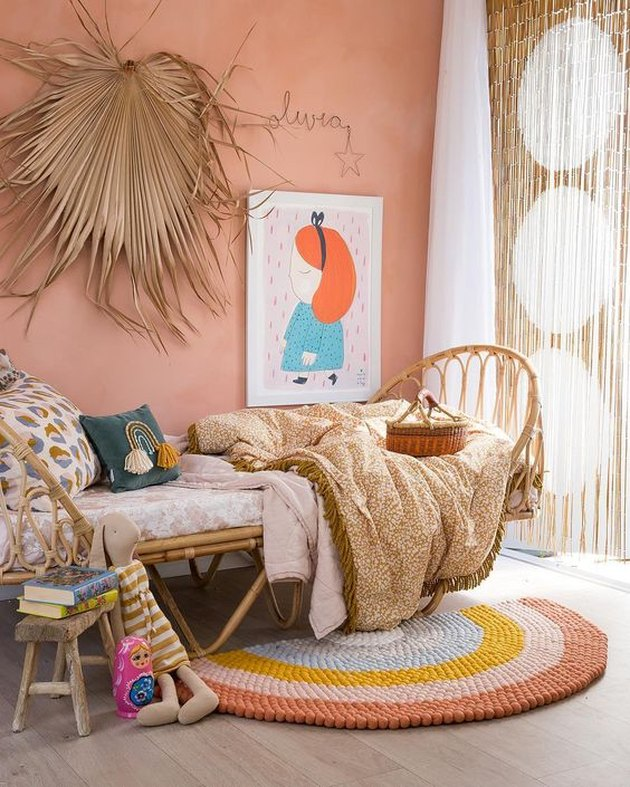 boho girls room with rattan bed and beaded curtain with pink walls