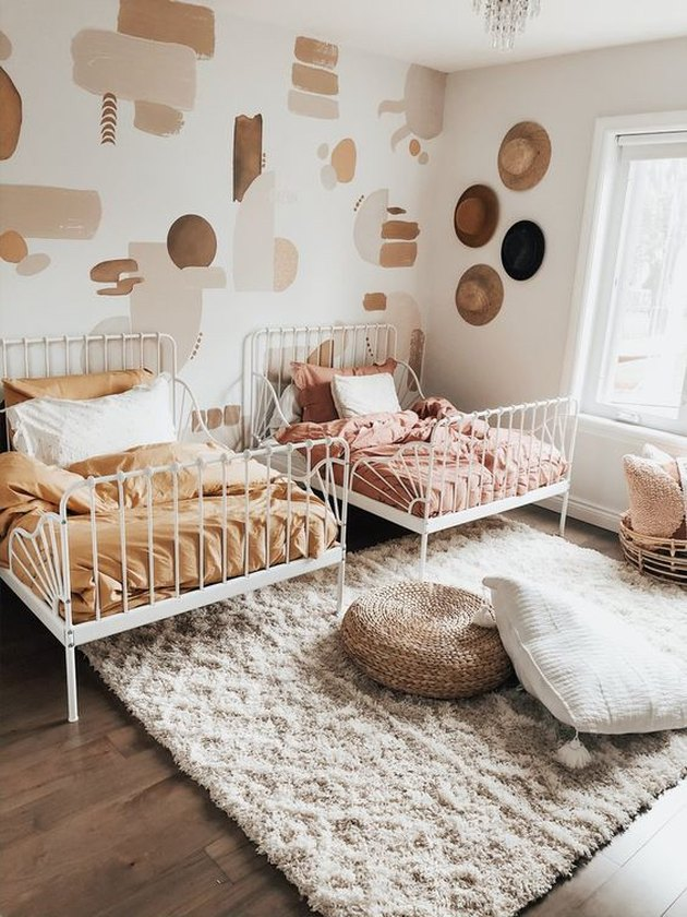 boho girls room with matching twin beds and decals on wall