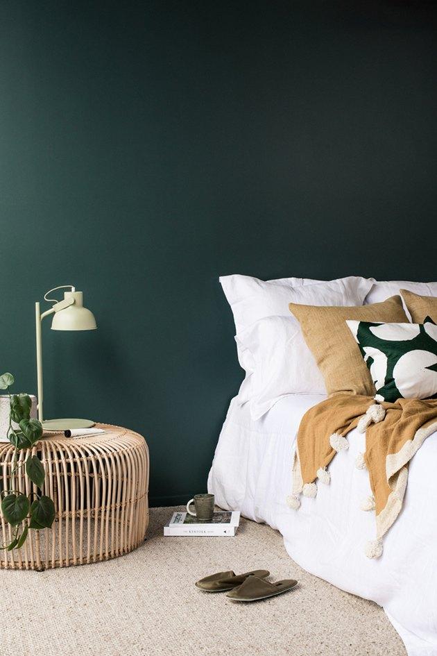 dark minimalist bedroom with rattan bedside table