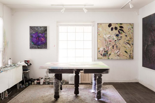 art studio in living room with art-filled walls