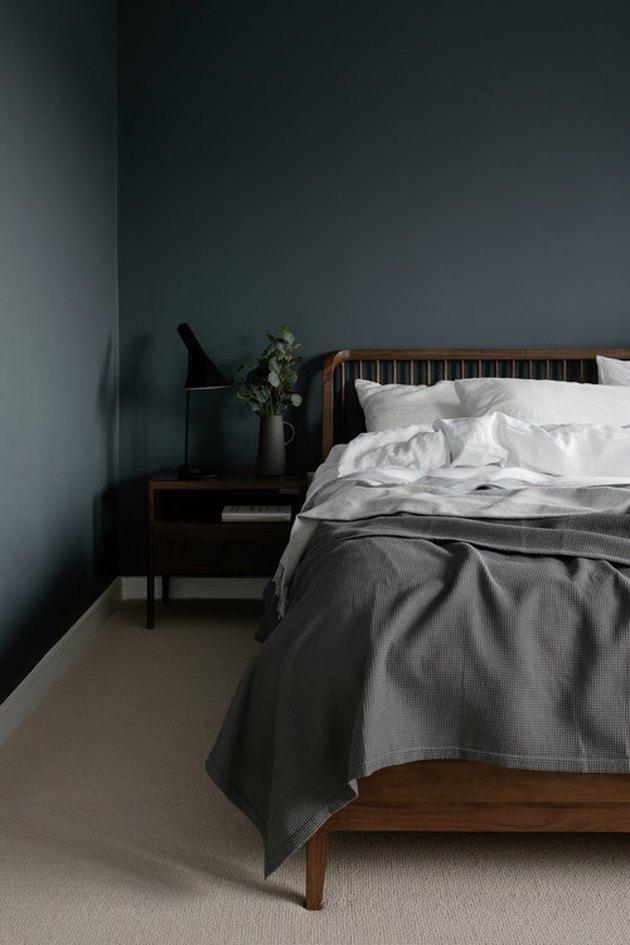 spindle bed frame in dark minimalist bedroom