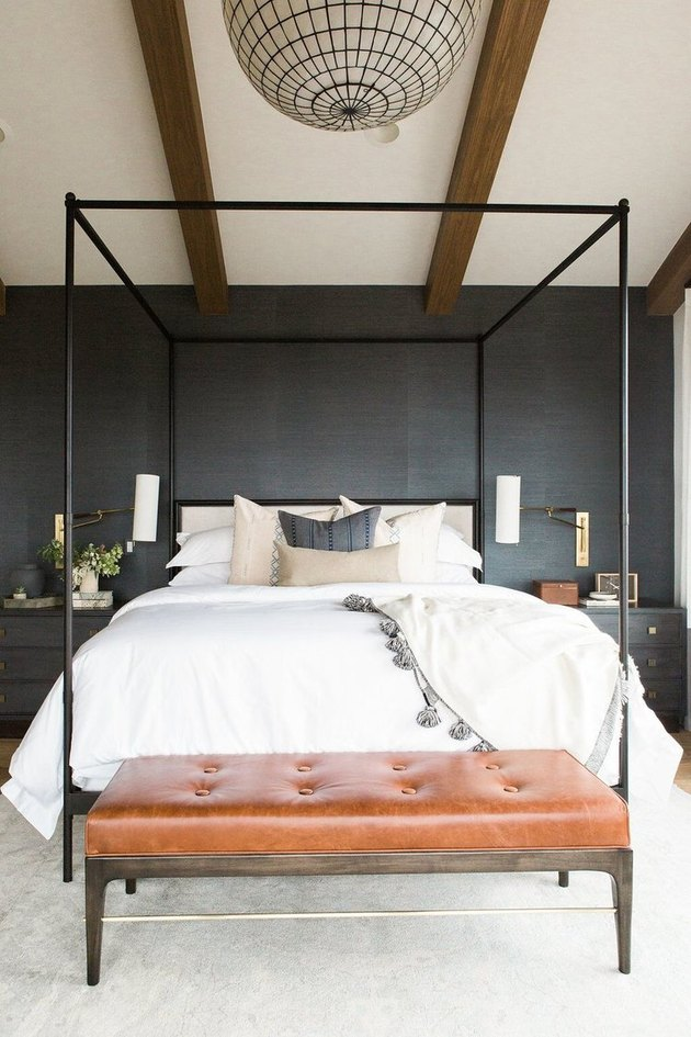 dark minimalist bedroom with brown leather bench and canopy bed,