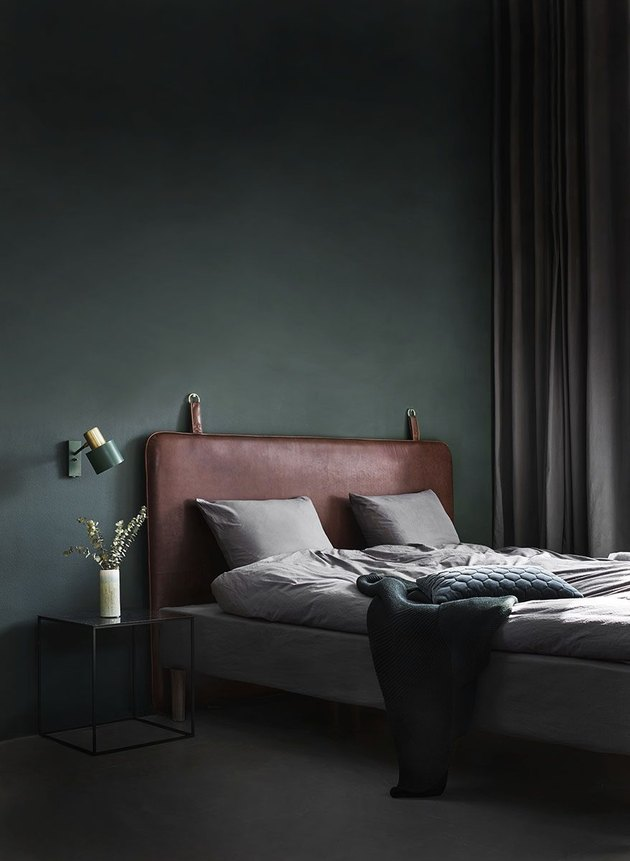 leather headboard in dark minimalist bedroom with turquoise wall sconce