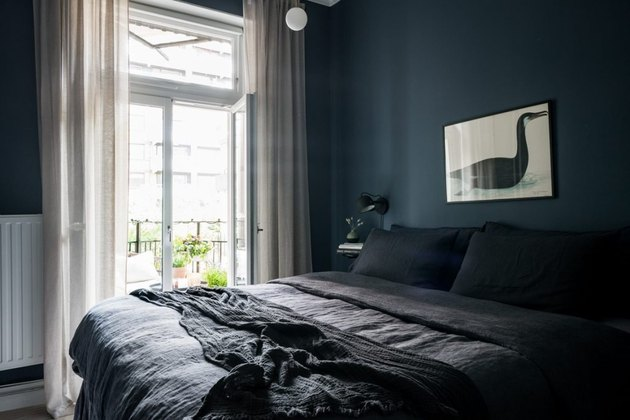 dark minimalist bedroom with deep blue wall paint and white curtains