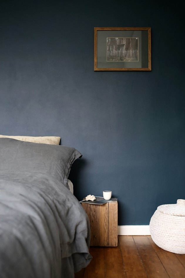 dark minimalist bedroom with wood box nightstand and dark blue wall