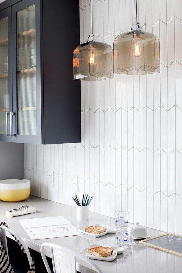 Minimal white tile art deco backsplash with pendant lights and blue cabinets
