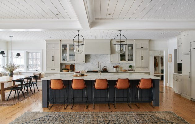 Blue and gray kitchen with cognac bar stools and white shiplap ceiling