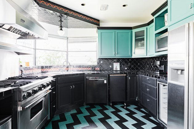 Teal green and black kitchen with chevron floor design