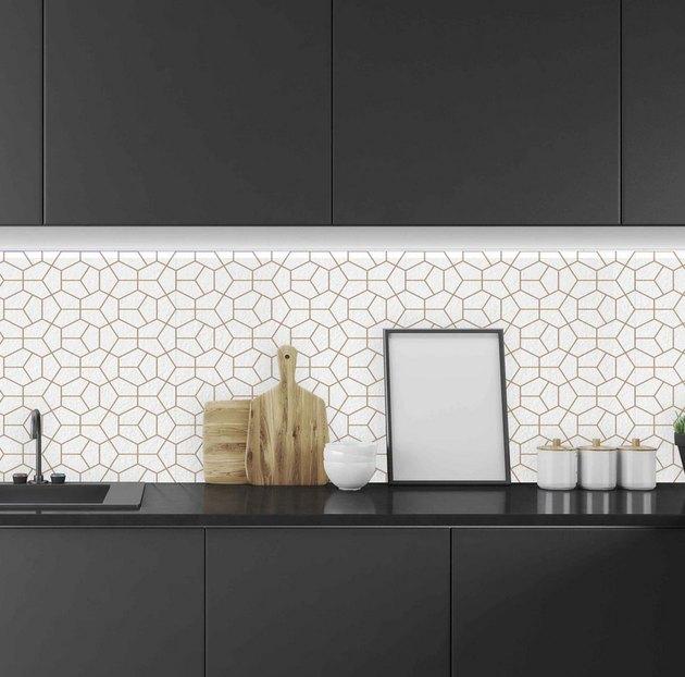 Geometric white and gold art deco backsplash with black kitchen cabinets