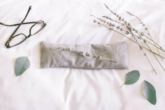 Gray linen eye pillow on top of white pillow with dried lavender