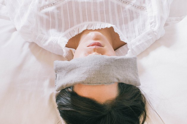 Gray linen eye pillow over sleeping woman's eyes