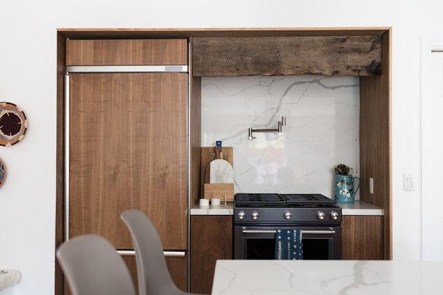focus on stove with wood cabinet surround, marble backsplash, pot fillerf aucet