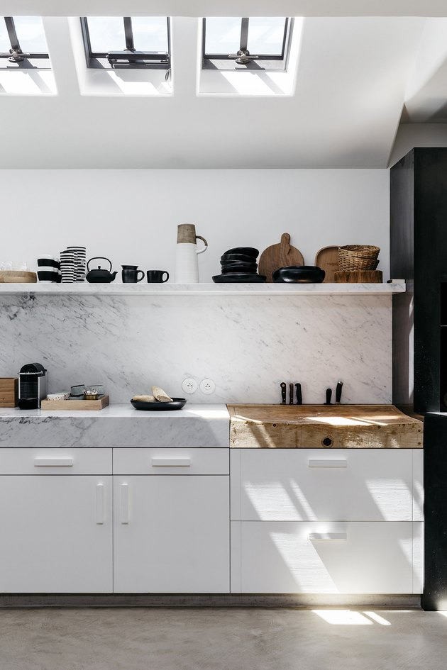 marble kitchen with thick countertops and wooden butchers block