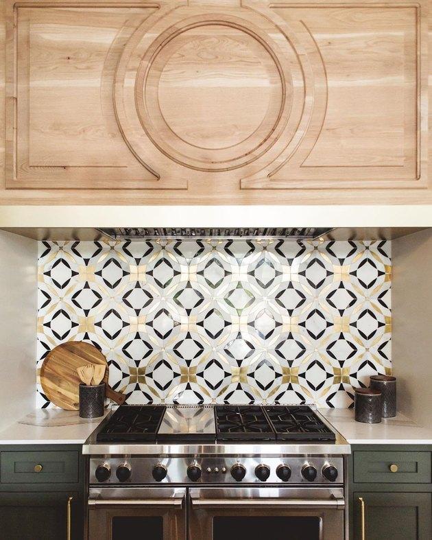 Brass, black, and white art deco backsplash with geometric shapes alongside green cabinets