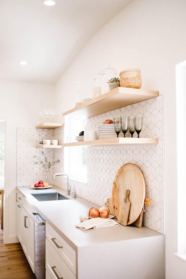 White tile art deco backsplash with geometric shapes in modern kitchen