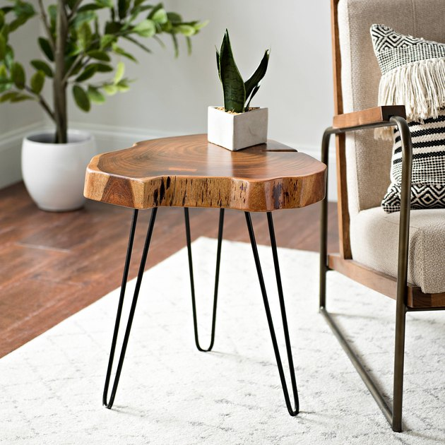 Small wooden raw-edge side table with three minimal black metal legs