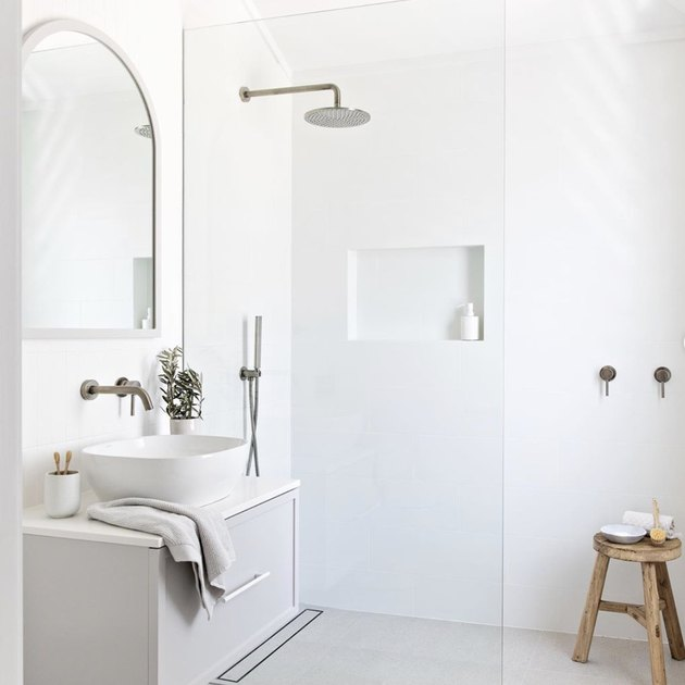 Minimalist bathrooms with shower and arched vanity mirror