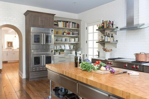 stainless steel kitchen island with butcher block counter in kitchen with double ovens
