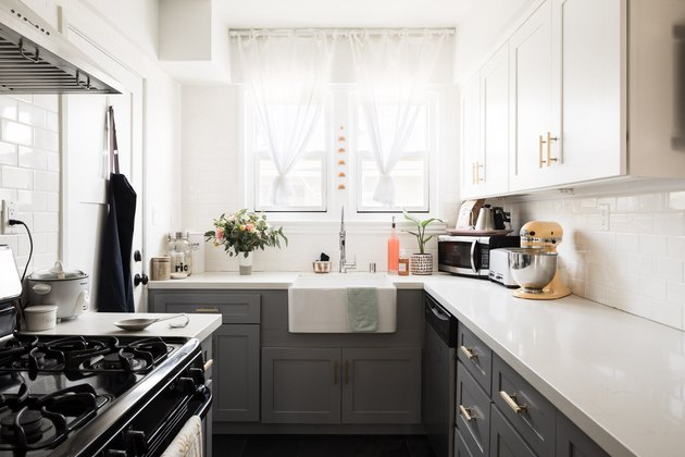 galley style kitchen with farmhouse sink, white countertops and grey kitchen cabinets