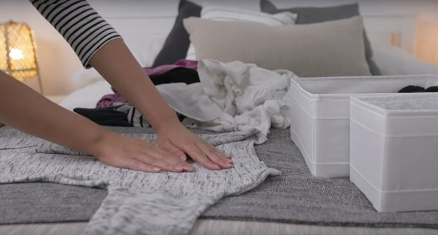 person folding shirt