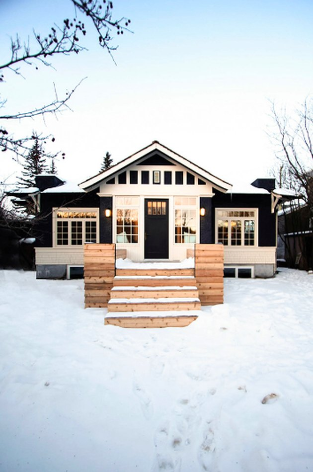 black craftsman house with white trim and natural materials