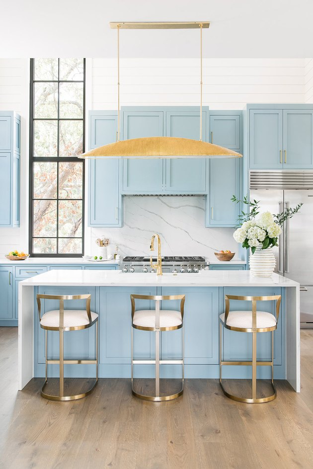 pastel blue kitchen island with marble waterfall countertop