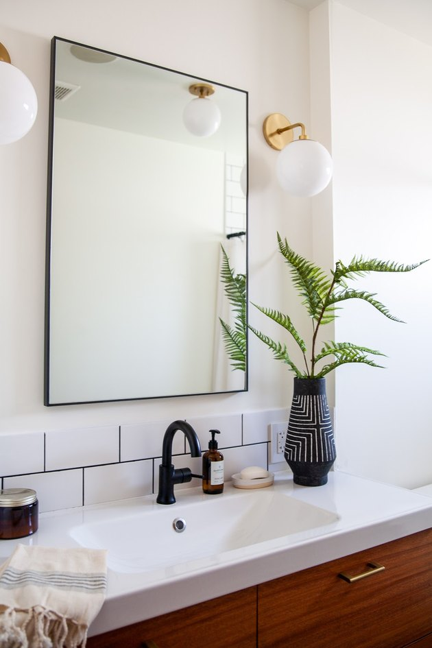 midcentury bathroom wall lighting idea in white bathroom with glass orb wall sconces