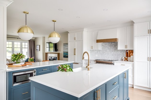 double blue kitchen island with brass accents and white countertop
