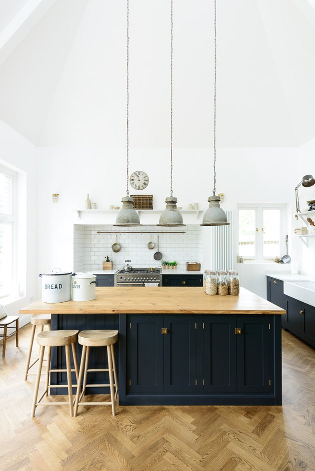navy blue kitchen island with wood countertop and herringbone flooring