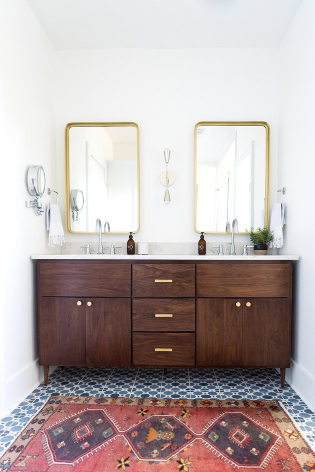 wood vanity with blue floor tiles and red runner