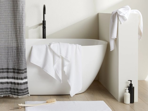 bathtub with gray curtain nearby and white towels
